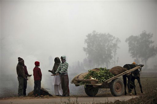 Indian vendors warm themselves near a fire on a cold and foggy morning in Jammu, India, Tuesday, Jan. 8, 2013. North India continues to face below average weather conditions with dense fog affecting flights and trains. More than 100 people have died of exposure as northern India deals with historically cold temperatures. &#40;AP Photo&#47;Channi Anand&#41; <span class=meta>(AP Photo&#47; Channi Anand)</span>