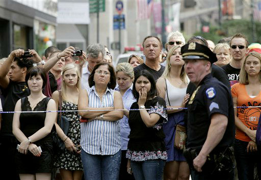 "<div class=""meta ""><span class=""caption-text "">Bystanders and a police officer stand on Fifth Avenue to view the scene after a multiple shooting outside the Empire State Building, Friday, Aug. 24, 2012, in New York. At least four people were shot on Friday morning and the gunman was dead, New York City officials said. A witness said the gunman was firing indiscriminately. Police said as many as 10 people were injured, but it is unclear how many were hit by bullets. A law enforcement official said the shooting was related to a workplace dispute. The official spoke on condition of anonymity because the investigation was ongoing.  (AP Photo/Mark Lennihan) (AP Photo/ Mark Lennihan)</span></div>"