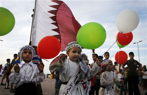 Palestinian children wave colored balloons and Qatari flags while waiting for the convoy of Emir of Qatar Sheikh Hamad bin Khalifa al-Thani, not pictured, to pass by a street in Gaza City, Tuesday, Oct. 23, 2012. The emir of Qatar received a hero&#39;s welcome in Gaza on Tuesday, becoming the first head of state to visit the Palestinian territory since the Islamist militant Hamas seized control there in 2007. &#40;AP Photo&#47;Hatem Moussa&#41; <span class=meta>(AP Photo&#47; Hatem Moussa)</span>