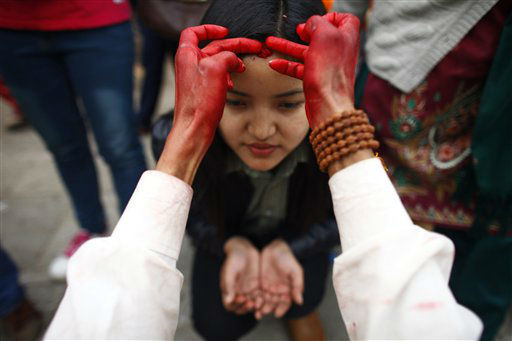 A priest applies tilak or vermilion powder mixed with rice, on a girl&#39;s forehead outside a Hindu temple meant for Goddess Saraswati to mark Saraswati puja festival, in Katmandu, Nepal, Friday, Feb. 15, 2013. Saraswati Puja, is a special day for students when they show their respect to Saraswati, the goddess of knowledge and learning. Children are given their first writing and reading lessons during this festival. &#40;AP Photo&#47;Niranjan Shrestha&#41; <span class=meta>(AP Photo&#47; Niranjan Shrestha)</span>