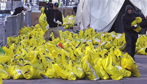 Workers find bags containing runners&#39; personal effects as they return them to their owner near the finish line of the Boston Marathon, after explosions killed three and injured more than 140 in Boston, Tuesday, April 16, 2013. The bombs that blew up seconds apart at the finish line of one of the world&#39;s most storied races left the streets spattered with blood and glass, and gaping questions of who chose to attack at the Boston Marathon and why. &#40;AP Photo&#47;Charles Krupa&#41; <span class=meta>(AP Photo&#47; Charles Krupa)</span>