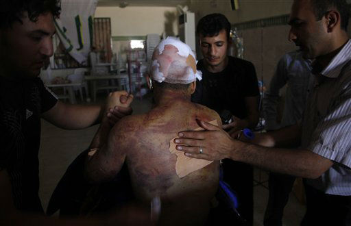 "<div class=""meta ""><span class=""caption-text "">Mahmoud, a 21-year-old Palestinian resident of Syria, receives treatment in a field hospital after he was found Monday, Aug. 6, 2012, with three gunshot wounds in the town of Anadan on the outskirts of Aleppo, Syria. Mahmoud, who would give only one name, described being the only survivor of a massacre in which he and 10 other men were blindfolded, beaten and sprayed with bullets. (AP Photo) (AP Photo/ AP)</span></div>"