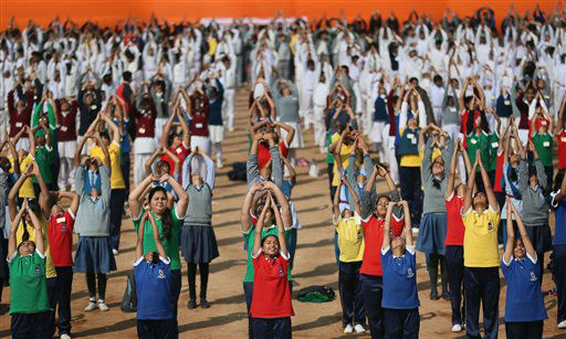 Indian school children perform Surya Namaskar or Sun salutation during a function to mark 150th birth  anniversary of Swami Vivekananda, in New Delhi, India, Monday, Feb. 18, 2013. Hundreds of school children across India performed Surya Namaskar, a Yoga posture which comprises 12 different bodily postures that ought to be performed in particular sequence. Swami Vivekananda, an Indian Hindu monk, who spread the message of India&#39;s spiritual heritage across the world. &#40;AP Photo&#47;Manish Swarup&#41; <span class=meta>(AP Photo&#47; Manish Swarup)</span>