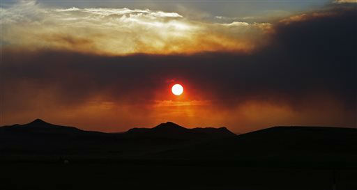 The sun sets through wildfire smoke Sunday, June 23, 2013, near Monte Vista, Colo. A large wildfire near a popular summer retreat in southern Colorado continues to be driven by winds and fueled by dead trees in a drought-stricken area, authorities said. &#40;AP Photo&#47;Gregory Bull&#41; <span class=meta>(AP Photo&#47; Gregory Bull)</span>