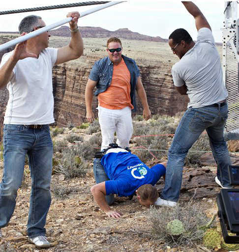 Aerialist Nik Wallenda kisses the ground after walking a 2-inch-thick steel cable that took him a quarter mile over the Little Colorado River Gorge in northeastern Arizona on Sunday, June 23, 2013. The daredevil successfully traversed the tightrope strung 1,500 feet above the chasm near the Grand Canyon in just more than 22 minutes, pausing and crouching twice as winds whipped around him and the cable swayed. &#40;AP Photos&#47;Discovery Channel, Tiffany Brown&#41; <span class=meta>(AP Photo&#47; Tiffany Brown)</span>