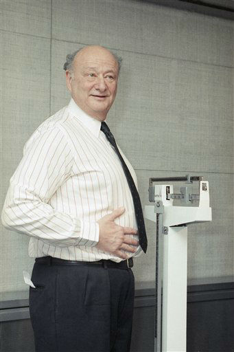 Former New York City Mayor Edward I. Koch pats his protruding tummy for reporters as he weighs in at a New York news conference, Jan. 4, 1990. The former mayor plans to pit his 244 pounds against a Slim Fast weight loss program. &#40;AP Photo&#47;Marty Lederhandler&#41; <span class=meta>(AP Photo&#47; Marty Lederhandler)</span>