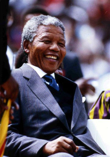 A jovial Nelson Mandela takes his seat in Soweto's Jabulani Stadium, Feb. 13, 1990, before addressing a crowd of 120,000 who packed the venue to hear him speak. Mandela, leader of the African National Congress, was released from from prison two days before. (AP Photo)