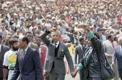 FILE - The Feb. 13, 1990 file photo shows released ANC leader Nelson Mandela and wife Winnie giving the black power salute on entering Soweto&#39;s city soccer stadium,. A crowd of an estimated 120,000 people crammed the venue to hear him speak.   On Sunday, before a global TV audience, Soccer City stadium will be the grand stage for a World Cup final. For many South Africans, the site has been hallowed ground for two decades _ not because of sports, but as a historic venue in the anti-apartheid struggle. In October 1989, with apartheid still in force, Soccer City&#39;s precursor stadium hosted an electrifying rally at which more than 70,000 blacks greeted newly freed leaders of the still-outlawed African National Congress _ most of its long-imprisoned hierarchy except Nelson Mandela.  Less than four months later, an even bigger, more euphoric crowd overflowed FNB Stadium to welcome home Mandela himself, the paramount ANC leader, at last freed unconditionally by the white-minority government after 27 years in prison.   &#40;AP Photo&#41; <span class=meta>(AP Photo&#47; Anonymous)</span>