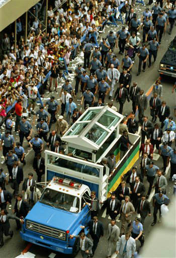 "<div class=""meta ""><span class=""caption-text "">New York City police surround the ""Mandelamobile"" during the parade up Broadway in New York, Wednesday June 21, 1990 for Nelson Mandela. The specially designed flatbed truck with a bulletproof glass bubble cost $58,000. Three-thousand police were assigned to prptect the 71-year-old civil rights leader. (AP Photo/George Widman) (AP Photo/ GEORGE WIDMAN)</span></div>"
