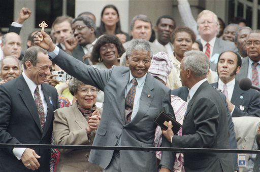 Nelson Mandela, center, is flanked by New York Governor Mario Cuomo, left, and New York City Mayor David Dinkins, right, as he holds up the key to the city presented to him during welcoming ceremonies at City Hall in New York on June 21, 1990 as Mandela began a three-day visit to the city. &#40;AP Photo&#47;Marty Lederhandler&#41; <span class=meta>(AP Photo&#47; Marty Lederhandler)</span>