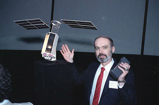 Motorola director of systems engineering, Ray Leopold, stands with a mock-up of one of the Iridium Satellites and a cellular phone, June 26, 1990, at the Hayden Planetarium in New York.  The Iridium would allow worldwide satellite telephone communication through a network of 77 satellites.  &#40;AP Photo&#41; <span class=meta>(AP Photo&#47; XMB RCC)</span>