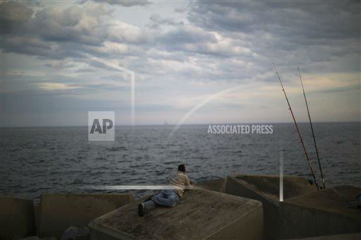 "<div class=""meta image-caption""><div class=""origin-logo origin-image ""><span></span></div><span class=""caption-text"">A man watches the Mediterranean sea near to his fishing rods at the port of Barcelona, Spain, Tuesday, May 7, 2013. (AP Photo/Emilio Morenatti)  </span></div>"