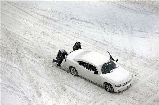 "<div class=""meta ""><span class=""caption-text "">Two men help push a car down a snow-covered street Thursday, Feb. 21, 2013, in St. Louis. Blinding snow bombarded much of the nation's midsection Thursday, causing whiteout conditions, making major roadways all but impassable and shutting down schools and state legislatures. (AP Photo/Jeff Roberson) (AP Photo/ Jeff Roberson)</span></div>"