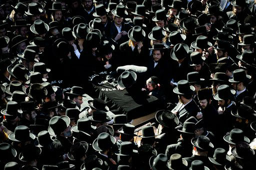 Members of the Satmar Orthodox Jewish community grieve over the coffins at the funeral for two expectant parents who were killed in a car accident, Sunday, March 3, 2013, in the Brooklyn borough of New York. A driver struck the car the couple were riding in early Sunday morning, killing both parents while their baby, who was born prematurely, survived and is in critical condition. &#40;AP Photo&#47;John Minchillo&#41; <span class=meta>(AP Photo&#47; John Minchillo)</span>