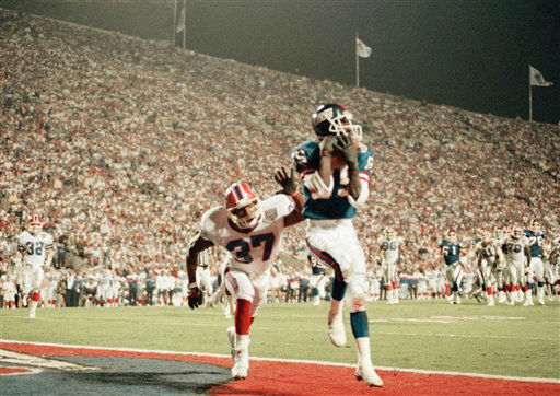 New York Giants wide receiver Stephen Baker (85) hauls in a touchdown pass in the endzone from quarterback Jeff Hostetler in the final minutes of the first half at Tampa Stadium on Jan. 27, 1991. The touchdown made the score 12-10 in favor of the Bills at the end of the first half. Diving after Bakers is Bills defensive back Nate Odomes (37). (AP Photo/Bill Waugh)