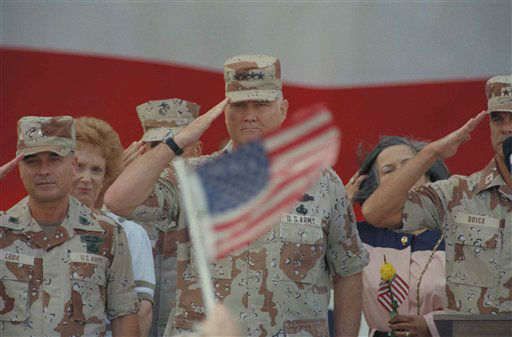 Gen. H. Norman Schwarzkopf salutes while a spectator waves a flag during welcome ceremonies Sunday morning at MacDill Air Force Base in Tampa, Fla., April 21, 1991. Schwarzkopf returned home after leading the allied victory in the Persian Gulf. &#40;AP Photo&#47;Lynne Sladky&#41; <span class=meta>(AP Photo&#47; Lynne Sladky)</span>