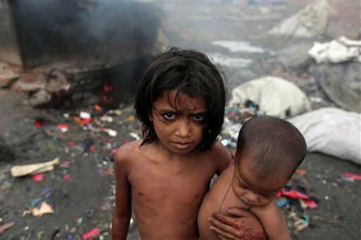 "<div class=""meta ""><span class=""caption-text "">A Bangladeshi girl carries a child and stands in front of a burner at a tannery on the banks of the Buriganga River in Dhaka, Bangladesh, Wednesday, Oct. 10, 2012. In a report released Tuesday, New York-based Human Rights Watch says tannery workers in Bangladesh's capital are being exposed to serious health risks because of hazardous chemicals and are in danger of accidents due to tannery machinery. Bangladesh annually exports millions of dollars of leather goods to some 70 countries, including the U.S. and Japan. (AP Photo/A.M. Ahad) (AP Photo/ A.M. Ahad)</span></div>"