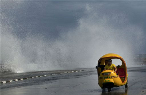 A man drives his Coco-taxi as a wave crashes against the Malecon after the passing of Hurricane Sandy in Havana, Cuba, Thursday, Oct. 25, 2012.  Hurricane Sandy blasted across eastern Cuba on Thursday as a potent Category 2 storm and headed for the Bahamas after causing at least two deaths in the Caribbean. &#40;AP Photo&#47;Ramon Espinosa&#41; <span class=meta>(AP Photo&#47; Ramon Espinosa)</span>