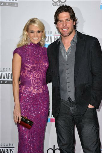 Carrie Underwood, left, and her husband Mike Fisher arrive at the 40th Anniversary American Music Awards on Sunday, Nov. 18, 2012, in Los Angeles. &#40;Photo by John Shearer&#47;Invision&#47;AP&#41; <span class=meta>(AP Photo&#47; John Shearer)</span>