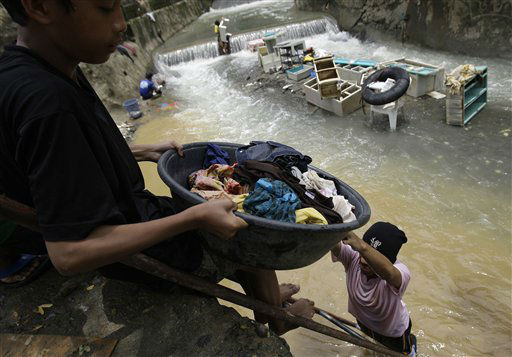 Residents clean their clothes along a river as floods recede in suburban Marikina city, east of Manila, Philippines, Friday Aug. 10, 2012. Philippine disaster officials were shifting Friday from rescue work to a massive clean-up of the capital following nonstop rains that left tons of muck and debris from floods littering the city. &#40;AP Photo&#47;Aaron Favila&#41; <span class=meta>(AP Photo&#47; Aaron Favila)</span>