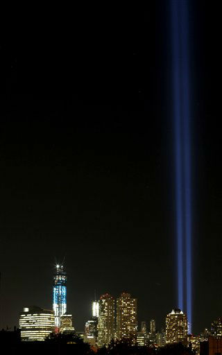 Two light beams, right, known as The Tribute in Light representing the Twin Towers illuminate the sky in Lower Manhattan near the One World Trade Center construction site, left, seen from Jersey City, N.J., in honor of the 11th anniversary of the Sept. 11 terrorist attacks, Tuesday, Sept. 11, 2012, in New York. &#40;AP Photo&#47;Julio Cortez&#41; <span class=meta>(AP Photo&#47; Julio Cortez)</span>