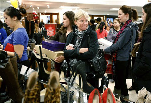 Cheryl Shedden, center right, of Beavercreek, Ohio, waits in the checkout line with her daughter Catie Smoot, center left, of Providence, R.I., at Macy's in downtown Boston, Friday, Nov. 23, 2012. Black Friday, the day when retailers traditionally turn a profit for the year, got a jump start this year as many stores opened just as families were finishing up Thanksgiving dinner.