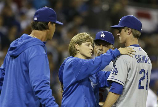Los Angeles Dodgers pitcher Zack Greinke is attended to by the team trainer Sue Falsone as manager Don Mattingly, left, and coach Davey Lopes look on during an interlude of a braw that started when Greinke hit San Diego Padres&#39; Carlos Quentin with a pitch in the sixth inning of baseball game in San Diego, Thursday, April 11, 2013. The battle restarted moments later. &#40;AP Photo&#47;Lenny Ignelzi&#41; <span class=meta>(AP Photo&#47; Lenny Ignelzi)</span>