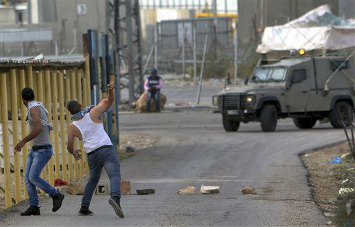 Palestinian youths throw stones at the direction of an Israeli army jeep during a protest against the Israeli military operations in Gaza Strip, close to the Israeli checkpoint of Al-Jalameh, north of the West Bank city of Jenin, Saturday, Nov. 17, 2012. Israel bombarded the Hamas-ruled Gaza Strip with nearly 200 airstrikes early Saturday, the military said, widening a blistering assault on Gaza rocket operations by militants to include the prime minister&#39;s headquarters, a police compound and a vast network of smuggling tunnels. &#40;AP Photo&#47;Mohammed Ballas&#41; <span class=meta>(AP Photo&#47; Mohammed Ballas)</span>
