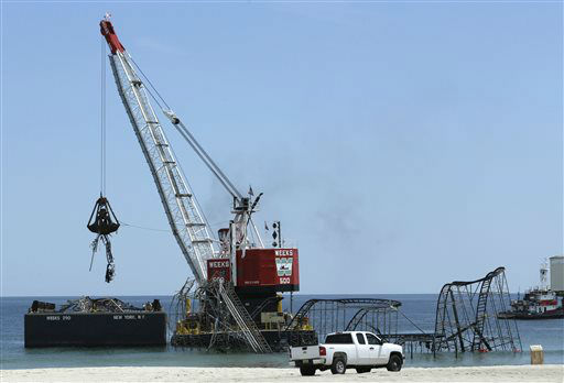 The claw of a crane, left, dumps part of the structure of the Jet Star Roller Coaster during demolition, Tuesday, May 14, 2013, in Seaside Heights, N.J. Workers began to demolish the roller coaster, which fell in the ocean when part of the Casino Pier was washed away by Superstorm Sandy in October. &#40;AP Photo&#47;Julio Cortez&#41; <span class=meta>(AP Photo&#47; Julio Cortez)</span>