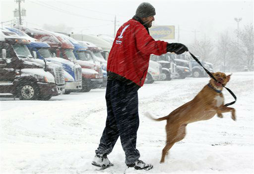 Trucker Ray Jersey of St. Louis exercises his dog Samson at a truck stop as snow falls in Council Bluffs, Iowa, Thursday, Feb. 21, 2013. Ray Jersey opted to wait the snow storm out as much of the nation&#39;s heartland is experiencing heavy snow, treacherous roads and a day off from work or school as a large, potentially dangerous winter storm pushed eastward out of the Rockies. &#40;AP Photo&#47;Nati Harnik&#41; <span class=meta>(AP Photo&#47; Nati Harnik)</span>