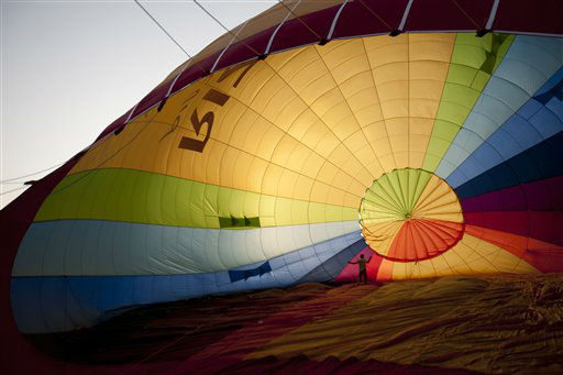 A hot air balloon crew member works ahead of the international hot air balloons festival during the Jewish holiday of Sukkot in Park Timna at the Araba Desert, southern Israel, Israel,Wednesday, Oct. 3, 2012. &#40;AP Photo&#47;Ariel Schalit&#41; <span class=meta>(AP Photo&#47; Ariel Schalit)</span>