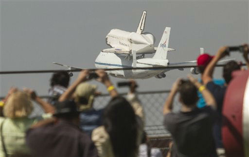 Spectators watch as space shuttle Endeavour, atop NASA's Shuttle Carrier Aircraft, prepares to land at Los Angeles International Airport Friday, Sept. 21, 2012. In a few weeks Endeavour will be towed through city streets to its new home at the California Science Center in downtown Los Angeles. (AP Photo/Ringo H.W. Chiu)
