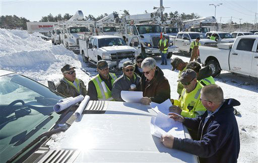 With more than a hundred trucks waiting to deploy, National Grid and utility workers from South Carolina meet on the hood of a pick-up truck to discuss their plan to re-energize towns without power at the Hanover Mall in Hanover, Mass., Sunday, Feb. 10, 2013.  A howling storm across the Northeast left the New York-to-Boston corridor shrouded in 1 to 3 feet of snow Saturday, stranding motorists on highways overnight and piling up drifts so high that some homeowners couldn&#39;t get their doors open. More than 650,000 homes and businesses were left without electricity. &#40;AP Photo&#47;Charles Krupa&#41; <span class=meta>(AP Photo&#47; Charles Krupa)</span>