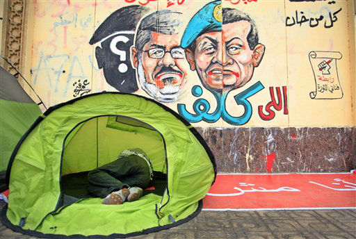 An opponent of Egypt&#39;s Islamist President Mohammed Morsi sleeps in a tent next to a wall graffiti with Arabic writing reads who assigned you did not die&#34;  as he and others protest outside the presidential palace in Cairo, Egypt, Tuesday, July 2, 2013. Egypt was on edge Tuesday following a &#34;last-chance&#34; ultimatum the military issued to Mohammed Morsi, giving the president and the opposition 48 hours to resolve the crisis in the country or have the army step in with its own plan. &#40;AP Photo&#47;Khalil Hamra&#41; <span class=meta>(AP Photo&#47; Khalil Hamra)</span>
