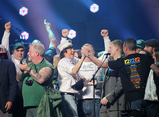 This image released by Starpix shows Paul McCartney, center, on stage with firefighters at the 12-12-12 The Concert for Sandy Relief at Madison Square Garden in New York on Wednesday, Dec. 12, 2012. Proceeds from the show will be distributed through the Robin Hood Foundation. &#40;AP Photo&#47;Starpix, Dave Allocca&#41; <span class=meta>(AP Photo&#47; Dave Allocca)</span>