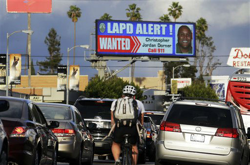 In this Feb. 8, 2013 photo, commuters on Santa Monica Boulevard on the Westside of Los Angeles see a digital billboard displaying a large &#34;wanted&#34; poster for former Los Angeles police Officer Christopher Dorner.  Dorner is suspected in a spree of violence as part of a vendetta against law enforcement after being fired by the department. He is also a suspect in the shooting deaths of a former LAPD captain&#39;s daughter and her fiance, and two other shootings that left an officer dead and two others wounded. Dorner&#39;s alleged killing spree hasn&#39;t just terrorized a large section of the country _ it has captured people&#39;s imagination and attention. &#40;AP Photo&#47;Reed Saxon&#41; <span class=meta>(AP Photo&#47; Reed Saxon)</span>