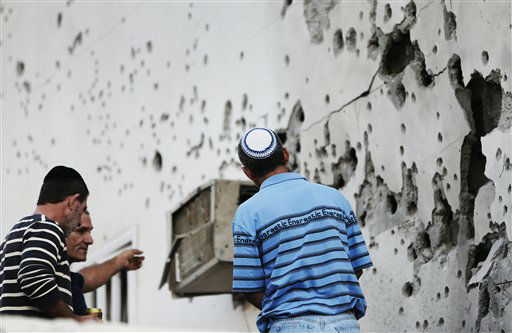 "<div class=""meta ""><span class=""caption-text "">Residents stand next to a damaged house after a rocket fired by Palestinian militants from inside the Gaza Strip, landed at the community of Ofakim, in southern Israel, Sunday, Nov. 18, 2012. Israel launched the operation last Wednesday by assassinating Hamas? military chief and carrying out dozens of airstrikes on rocket launchers and weapons storage sites. Over the weekend, the operation began to target Hamas government installations as well, including the offices of its prime minister and attacks on a major training base and the two media centers.  (AP Photo/Lefteris Pitarakis) (AP Photo/ Lefteris Pitarakis)</span></div>"