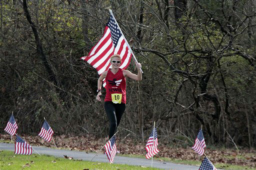 Kate Bielak from Natrona Heights, Pa., carries a flag as she finishes the Indiana First Bank Veterans Marathon in Saylor Park in Blairsville, Pa., Sunday, Nov. 11, 2012. Bielak&#39;s brother Army Capt. Jim Nemec of West Point, N.Y., who just returned from a tour of duty in Afghanistan was also running the marathon. &#40;AP Photo&#47;Gene J. Puskar&#41; <span class=meta>(AP Photo&#47; Gene J. Puskar)</span>