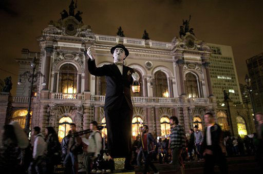 An artist dressed as Charles Chaplin performs in front of Municipal Theater as part of the annual art event Virada Cultural in Sao Paulo, Brazil, Saturday, May 18, 2013. The Virada Cultural or Cultural Turn, is an annual event organized, since 2005, to promote the city of Sao Paulo with 24 hours of uninterrupted artistic attractions that include music concerts, dance, cooking and theater. &#40;AP Photo&#47;Andre Penner&#41; <span class=meta>(AP Photo&#47; Andre Penner)</span>