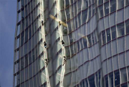 Reflected in a nearby building, Greenpeace protesters climb up The Shard, the tallest building in western Europe, during a protest against the oil company Shell&#39;s drilling in the Arctic, Thursday, July 11, 2013. &#40;AP Photo&#47;Sang Tan&#41; <span class=meta>(AP Photo&#47; Sang Tan)</span>