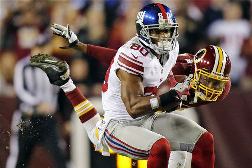 New York Giants wide receiver Victor Cruz &#40;80&#41; pulls in a pass under pressure from Washington Redskins defensive back Cedric Griffin during the first half of an NFL football game in Landover, Md., Monday, Dec. 3, 2012. &#40;AP Photo&#47;Evan Vucci&#41; <span class=meta>(AP Photo&#47; Evan Vucci)</span>