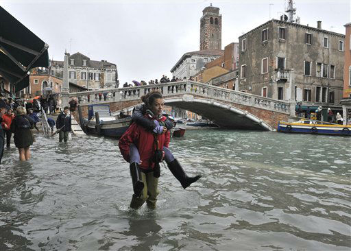 People walk in high water near the Ponte delle Guglie in Venice, Italy, Thursday, Nov. 1, 2012. High tides have flooded Venice, leading Venetians and tourists to don high boots and use wooden walkways to cross St. Mark&#39;s Square and other areas under water. Flooding is common this time of year and Thursday&#39;s level that reached a peak of 55 inches &#40;140 centimeters&#41; was below the 63 inches &#40;160 centimeters&#41; recorded four years ago in the worst flooding in decades. &#40;AP Photo&#47;Luigi Costantini&#41; <span class=meta>(AP Photo&#47; Luigi Costantini)</span>