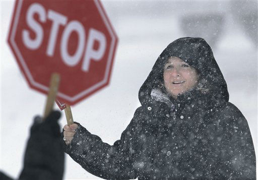 School crossing guards work outside school during a fast moving snow storm Thursday, Feb. 21, 2013, in Springfield, Ill. Blinding snow bombarded much of the nation&#39;s midsection causing white out conditions, making major roadways all but impassable and shutting down schools and state legislatures. &#40;AP Photo&#47;Seth Perlman&#41; <span class=meta>(AP Photo&#47; Seth Perlman)</span>