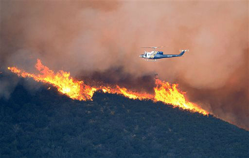 A water dropping helicopter gets ready to make a drop on a fire burring in Point Mugu State Park during a wildfire that burned several thousand acres, Thursday, May 2, 2013, in Ventura County, Calif.   &#40;AP Photo&#47;Mark J. Terrill&#41; <span class=meta>(AP Photo&#47; Mark J. Terrill)</span>