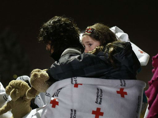 "<div class=""meta ""><span class=""caption-text "">Eight-year old Shayne Frate, a third grade student at Sandy Hook Elementary School, hangs from her mother Valerie's back, wrapped in a Red Cross blanket to protect her from the cold, rainy weather, as she waits in line to attend an interfaith vigil with President Barack Obama, Sunday, Dec. 16, 2012, in Newtown, Conn. A gunman walked into Sandy Hook Elementary School in Newtown Friday and opened fire, killing 26 people, including 20 children. (AP Photo/Jason DeCrow) (AP Photo/ Jason DeCrow)</span></div>"