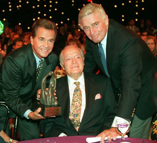 Family Film Awards producer Dick Clark, left, and Charlton Heston, right, turn to cameras as they present the Lifetime Achievement Award to the legendary performer Bob Hope at his table during ceremonies Thursday, Aug. 22, 1996 in Los Angeles. &#40;AP Photo&#47;Susan Sterner&#41; <span class=meta>(AP Photo&#47; SUSAN STERNER)</span>