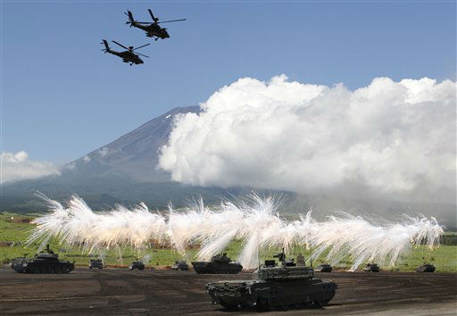 A line of Japan Ground Self-Defense Force tanks flare up a smoke screen during the annual live-firing exercise and demonstration at Higashi Fuji training range in Gotemba, southwest of Tokyo, Tuesday, Aug. 21, 2012. &#40;AP Photo&#47;Koji Sasahara&#41; <span class=meta>(AP Photo&#47; Koji Sasahara)</span>
