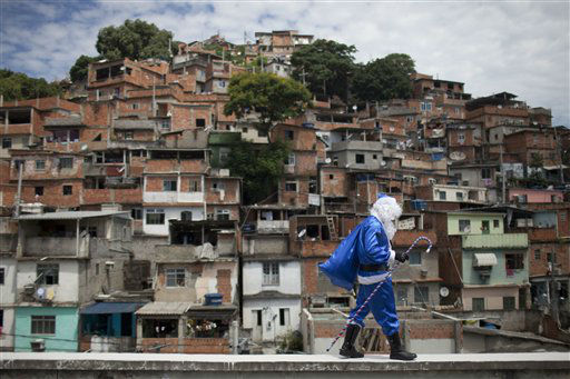 A police officer dressed in a Santa Claus costume, with the blue color representing the police, walks in Macacos slum after arriving in a police helicopter in Rio de Janeiro, Brazil, Thursday, Dec. 20, 2012. The Pacifying Police Unit, or UPP, organized for Santa to visit the pacified slum to hand out Christmas gifts to young residents. &#40;AP Photo&#47;Felipe Dana&#41; <span class=meta>(AP Photo&#47; Felipe Dana)</span>