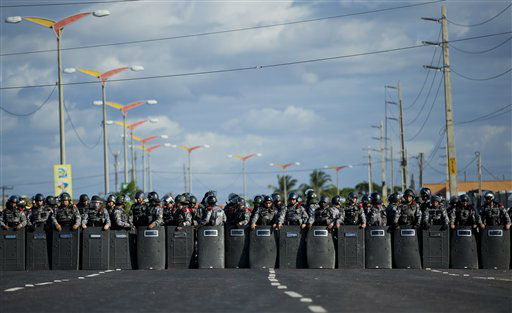 Riot police block a road  to prevent protesters from reaching the Castelao stadium before the start of a soccer Confederations Cup group B match between Nigeria and Spain in Fortaleza, Brazil, Sunday, June 23, 2013. Small gatherings occurred Sunday in a few cities, no clashes were reported. On Saturday a quarter-million Brazilians protested in more than 100 cities, but the gatherings were less violent than those seen earlier in the week. &#40;AP Photo&#47;Victor R. Caivano&#41; <span class=meta>(AP Photo&#47; Victor R. Caivano)</span>