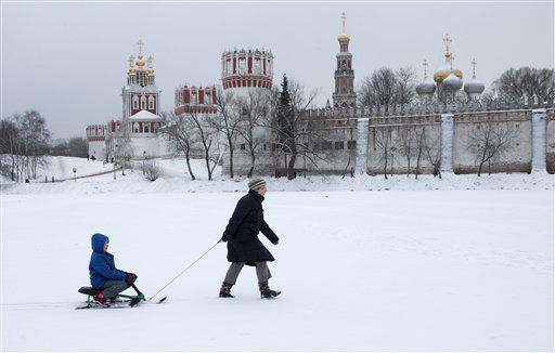 Woman pulls  a sled with a child on frozen pound in Moscow, Russia, Tuesday, Jan. 1, 2013. The 16th-century Novodevichy Convent is on background. &#40;AP Photo&#47;Misha Japaridze&#41; <span class=meta>(AP Photo&#47; Misha Japaridze)</span>